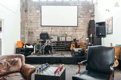 This space has a classic rock and roll vibe with brick walls, vintage-inspired furniture, upstairs loft space. The space features a relaxed atmosphere with throw-back decor, but professional and cutting edge sound equipment to function as a cool recording studio for a jam session.
