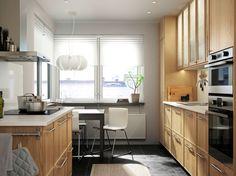 Cozinha em carvalho com bancadas em branco Combinada com forno em aço inoxidável, forno micro-ondas e exaustor