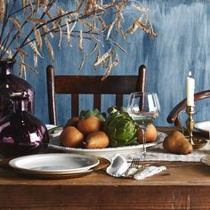 Seasonal touches like accents of dried plants, brass candlesticks, and dark amethyst bottles bring autumn inside without the chill.