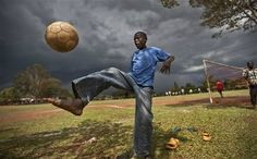 A boy plays with a soccer ball as a thunderstorm approaches at an annual soccer tournament and sports day in the village of Kogelo held in memory of President Barack Obama's late father, Barack Obama Sr., in western Kenya.  (Photo by Ben Curtis / AP). First published in the November 04, 2012, 1:08 p.m. edition (http://dailysource.org/pictures/show/42304).