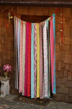 Rather cute fabric strip backdrop, easily made too... Would make a great fly curtain over the back door.