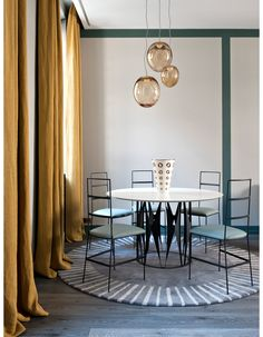 """Dans la salle à manger, un décor très géométrique. Table et chaises (Julie Prisca). Suspensions en verre soufflé (Atelier Areti). Rideaux """"Sauge Panama�..."""