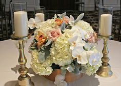 lush orchids, hydrangea, dusty miller, and roses are the perfect compliment to the pale gold candlesticks!