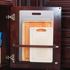 A cutting board holder that hides behind a base cabinet door ,Love this idea !