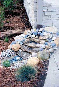 build up stone against the house for protection and the waterfall; elbow is hidden by rocks