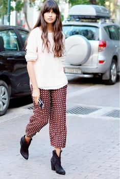 Beige sweater with printed pants and western booties for casual attire.