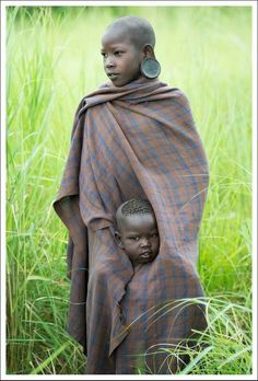 A Mursi girl from Ethiopia protects her young sibling. The Mursi are a pastoralist ethnic group. photo by John Kenny Kids Around The World, We Are The World, People Around The World, John Kenny, African Children, African Women, African Art, Beautiful Children, Beautiful People