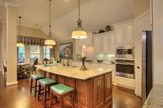 #Granite #counter tops and #teal accents make this kitchen shine. All #white #cabinets is a #classic.