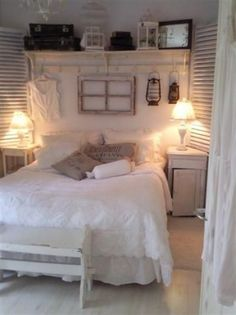 Brocante slaapkamer met oude luiken, landelijk wandrek, oude koffers, brocante kroonluchter met bloemen, linnen kussens en oude nachtkastjes.