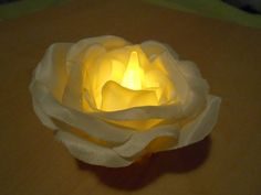 A tea light with fake rose petals hot glued to it