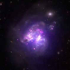 """Arp 299 is a system located about 140 million light years from Earth. It contains two galaxies that are merging, creating a partially blended mix of stars from each galaxy in the process.  However, this stellar mix is not the only ingredient. New data from Chandra reveals 25 bright X-ray sources sprinkled throughout the Arp 299 concoction. Fourteen of these sources are such strong emitters of X-rays that astronomers categorize them as """"ultra-luminous X-ray sources,"""" or ULXs.  (Credit…"""