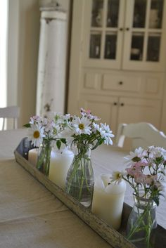 beautiful... chicken feeder used as centerpiece with simple daisies.