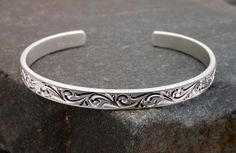 Solid sterling cuff bracelet. Hand engraved with mirrored bright cuts in a running leaf and spiral pattern. Frosty white satin finish creates a stunning contrast. The inside of the bracelet is engravable and can be inscribed with any special message. Handmade by Michael Dobrow of Sierra Silver Designs. $70