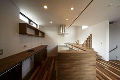 木材を重ねて造った腰壁が印象的なキッチン。背面のスペースには好みの収納を組み込み、カーテンで仕切って利用する。