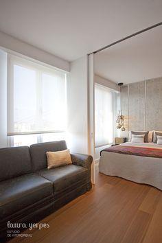 Habitación con zona estar, sistema de divisor realizado con unas puertas correderas con guía oculta en el techo.