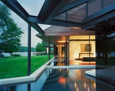 """A pool nearly surrounds the entire house, hence the name """"Peninsula House."""" The expansive glass doors can be slid open, and one can literally walk out from the living room and into the calm and modern pool for a quick, refreshing dip."""