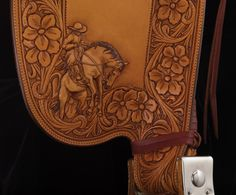 Three dramatic scenes of bronc riders adorn a Rick Bean saddle that begs to be ridden. Built on a 16-inch Wade tree, the 8-string saddle has...