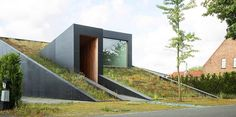 A sloping green roof hides the split level interior of Belgium\'s discrete House Pibo