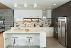 Beautiful Modern Kitchen. Multi-tone Subway Tile w/ White Stone counter top with waterfall edge.