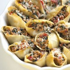 Sausage and Spinach Stuffed Shells -these look good - 16-18 jumbo pasta shells 1 pound fresh pork sausage links, casing removed 1 tablespoon minced garlic 1 (14-ounce) can diced tomatoes 1 cup frozen spinach, thawed and squeeze dry 1/2 cup ricotta cheese 1/2 cup shredded mozzarella cheese salt and freshly ground pepper