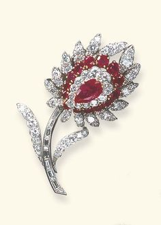 A RUBY AND DIAMOND FLOWER BROOCH, BY VAN CLEEF & ARPELS Centering upon a pear-shaped ruby pistil, within a three-tiered petal surround alternately-set with circular-cut rubies and diamonds, to the baguette-cut diamond undulating stem, extending circular-cut diamond leaves, mounted in platinum and gold