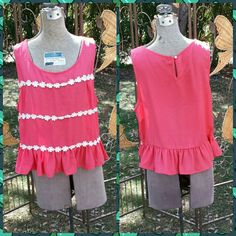 BOGO FREE SALECute Top w/ Ruffle & flower Applique This is a salmon colored top with 3 rows of flower applique. Round neck. Button at back if neck. Ruffle around bottom. There are some stains in the ruffle part of the shirt but are kind of hidden by it as seen in thr 3rd picture. Finn & Clover Tops Blouses