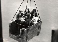 Leden van de Nederlandse band uit Amsterdam 'The Outsiders' spelen in een krat dat opgehesen wordt boven water. 1966.