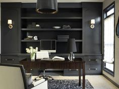 Matte or low glass black shelving with all back accessories in office - monochromatic look create distraction free zone.