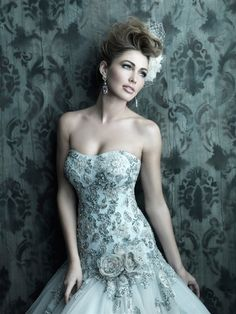 Stunning fitted A-line, wedding gown features lace applique, embroidery, and Swarovski crystals on English net. The fitted bodice has a slightly scooped neckline and floral accents at the waist.