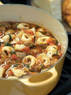 2 Tbsp. olive oil 1 onion, chopped 4 or 5 garlic cloves, crushed 5 or 6 Italian sausages (hot, mild, or sweet) or 1 lb of ground Italian sausage 1 tsp. oregano 1 tsp. rosemary ½ tsp. basil 2 cans stewed tomatoes 6 cups chicken broth 1 bag (about 12 oz.) fresh pre-washed spinach, chopped 1 package fresh or frozen tortellini Parmesan cheese, to taste Salt and pepper, to taste