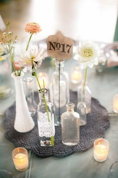 centerpiece of tiny glass bottles with simple flowers and table number