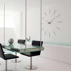 Exemplary designer high-end modern luxurious wall mounted analog clock finished in wenge wood and matte polished brass.