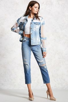 A midweight denim jacket  featuring sheer organza inserts, allover bleach splatters, a basic collar, button front closures, button flap chest pockets, slant front pockets, long sleeves, and frayed trim.
