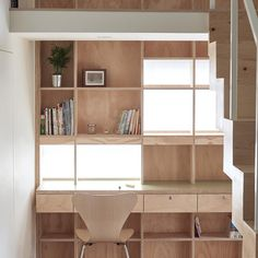 Next in our roundup of space-saving solutions is this double-storey bookcase which covers the wall behind a blocky staircase, integrating shelves, windows and a desk in a Taiwanese apartment.  Hao Design transformed this small apartment into a family home by creating an upper level to house a second bedroom and storage space. Find out more on dezeen.com/interiors #interiordesign #house #Taiwan
