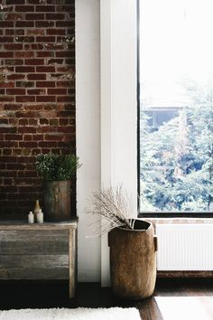 Exposed brick, wooden pot and black steel frame picture window. http://www.raftfurniture.co.uk/tall-teak-pot-natural-finish-1484.html