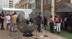 Visitors admire the Blue Iris Torus sculpture by David Harber while queuing outside the Gin Hut for delicious gin & tonics from Williams Chase Distillery #Focus16