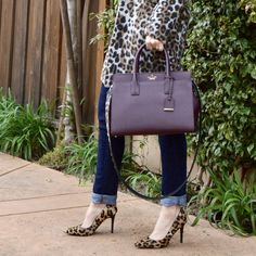 Leopard, style over 40, trendy over 40, style over 50, 40 plus style, winter to spring transitional outfits, OOTD, leopard coat, leopard pumps, criss cross tee, guitar strap trend