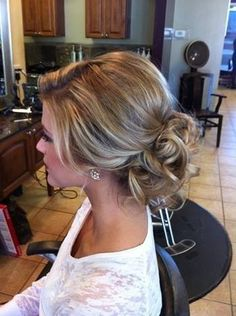 Low messy bun with volume on top.