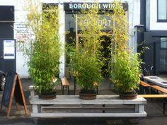 Bench on castors with holes for pots outside restaurant // L'entrepot, London E8