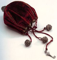 Velvet purse trimmed with silver thread and silver balls, holding silver key, the Netherlands, 1600. At the Hendrikje Bag Museum, the Netherlands. From Bags, Pepin Press, 2004.
