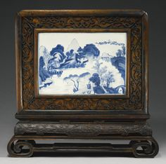A blue and white plaque mounted as a table screen, Qing dynasty, Kangxi period, the wood frame and stand 19th century