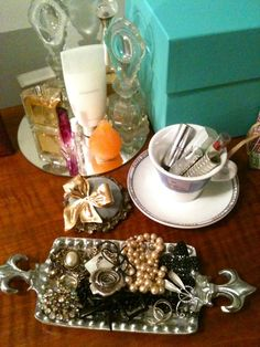Pretty Dresser - Using a mirror to displaying antique perfume bottles, a butter dish for favorite jewelry, a vintage pin cushion for pins, and a teacup for lipsticks.
