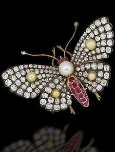 A pearl, ruby and diamond butterfly brooch, circa 1900 Mounted en tremblant, the wings pavé-set with old brilliant and rose-cut diamonds and decorated with bouton pearls of golden tint, the body set with a cushion-shaped ruby, the thorax with a bouton pearl, the eyes with cabochon rubies, mounted in silver and gold, French assay mark, width 5.3cm