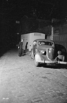 At 3:45am, Patience 'Boo' Brand drives the tea car and canteen from the WVS Canteen Service depot, whilst Rachel Bingham directs her by torchlight. They have together htiched the trailer onto the car and are on their way to supply refreshments to shelterers emerging for work after a night in the shelter.