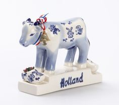Cow Of Holland by Barang Eropa. Mini statue of cow wearing a bell on its neck in blue and white color. It features a pair of clog and it written 'holland' below of the cow. It has size dimension; 8cm x 14cm x 13cm.  http://www.zocko.com/z/JJjT1