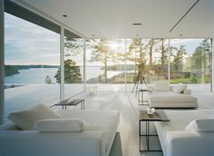 Modern Lake House Living Room / Overby House sits high on a Varmdo island cliffside overlooking the Baltic Sea. Designed as a summer getaway by John Robert Nilsson, the modern holiday house reflects the Swedish minimalist design aesthetic beautifully with clean forms and lines, pristine white palettes and natural light wood accents.