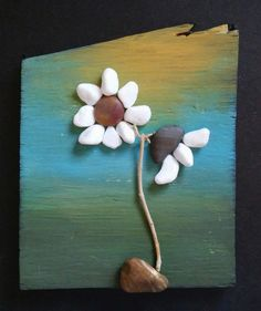 Original pebble and rock art depicting white flowers using all natural materials incl reclaimed wood, pebbles, twigs