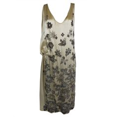1920's party dress is made from luxurious ivory silk satin that has been densely embroidered with shimmering glass beads on both front and back. Glistening gunmetal grey and silver beaded flowers cover the dress in gradient scale. Dress is gathered asymmetrically to one side, culminating in an elegant swag.