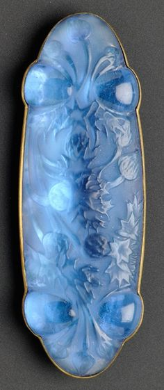 Moulded Blue Glass Brooch, René Lalique, probably from the 1920s. With thistle motifs, on a foiled ground, gilt-metal mount, signed. #Lalique #ArtDeco #brooch
