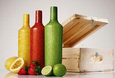 II. Les composants : Le contenant est une bouteille en verre recouverte d'un pelage à la texture et aux couleurs fruitées. Le décor original de par son pelage donne aux consommateurs l'impression de vrais fruits puisque avant de savourer le produit on peut le peler. De plus, les boites en bois dans lesquels sont vendus les bouteilles rappelles les cagettes dans lesquels les fruits sont vendus ce qui accentue le principe d'un produit et d'une communication en accord avec la nature.